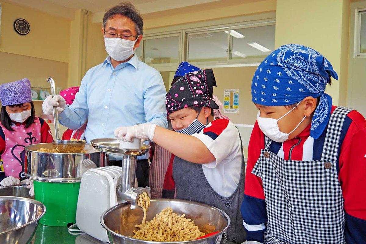 小山さん(右から3人目)のサポートを受けながらみそづくりに取り組む釜石小児童