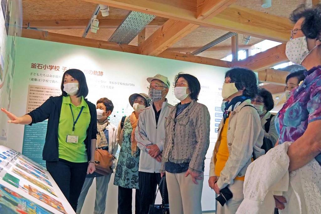 いのちをつなぐ未来館を見学する平田いきいきサークルの会員。川崎さん(左)の説明に耳を傾けた
