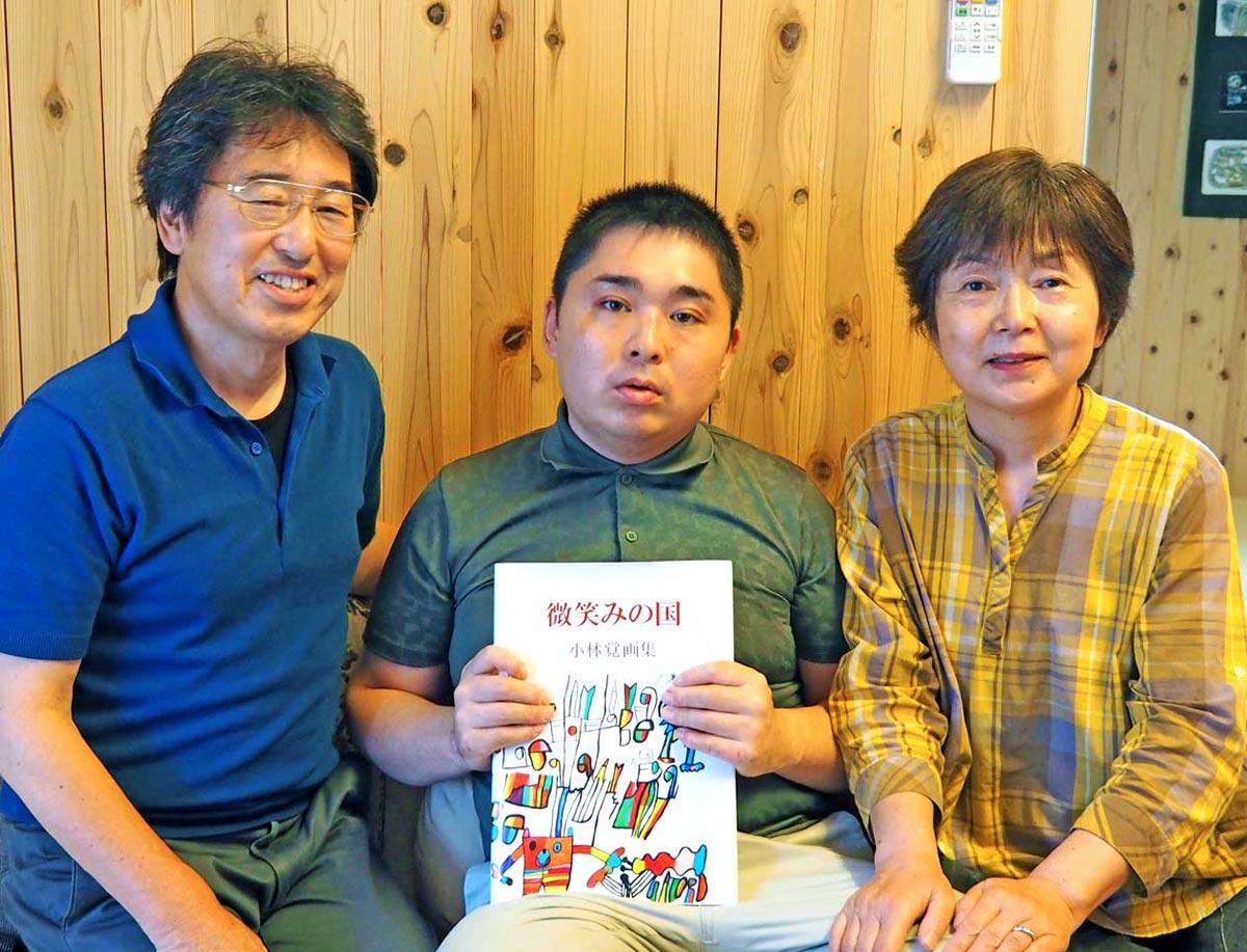 画集を手にする小林覚さん(中)、寄り添う家族