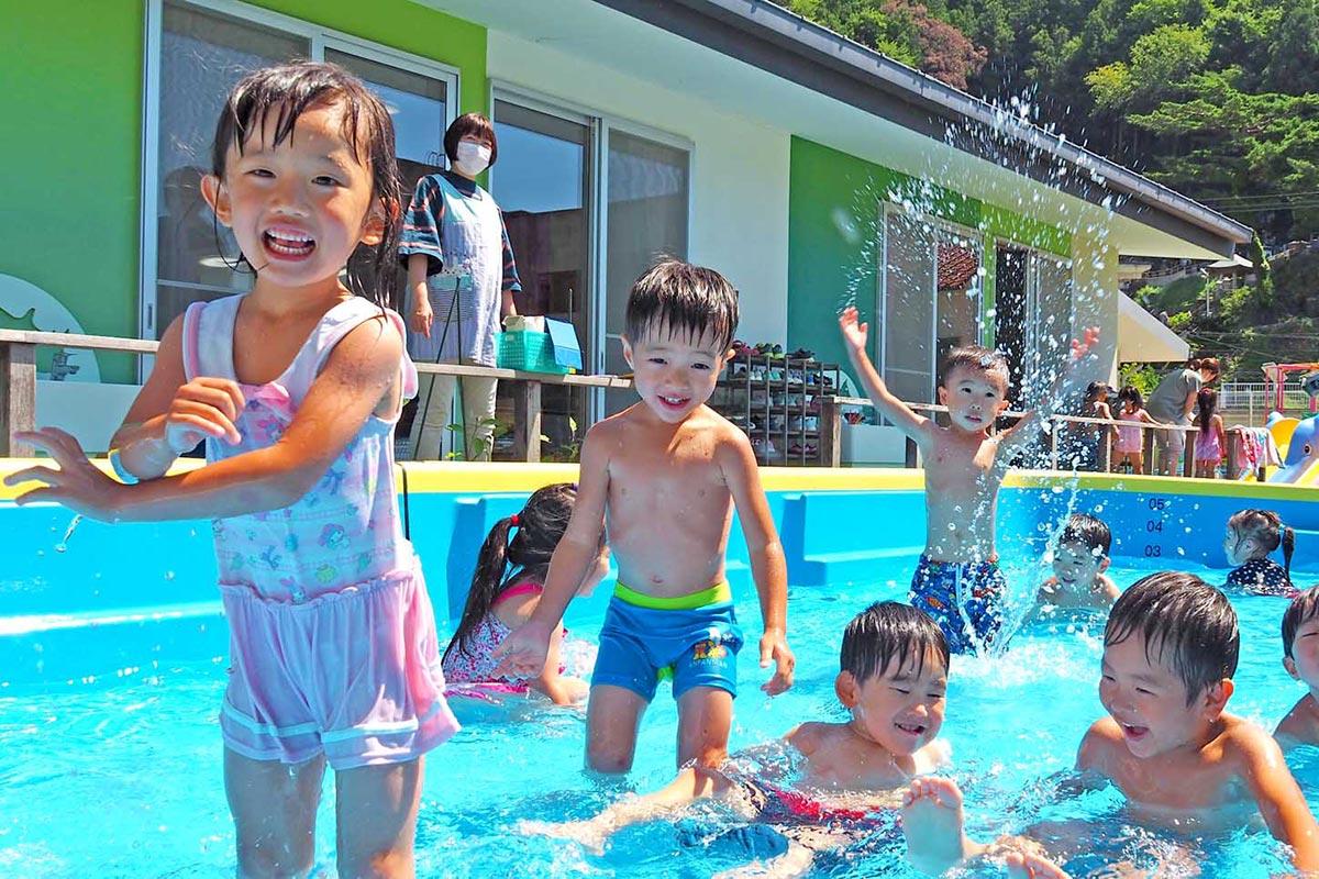 水しぶきをあげ、園庭のプール遊びを満喫する園児