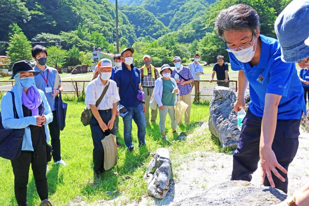 旧鉱山事務所前で化石が入った岩などを見学する参加者