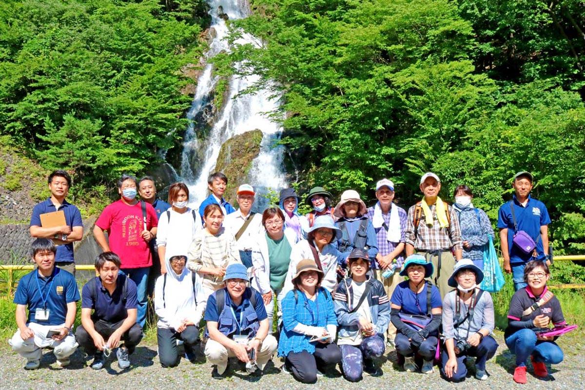 ズリ堆積場脇から流れ出る人工の滝の前で記念撮影