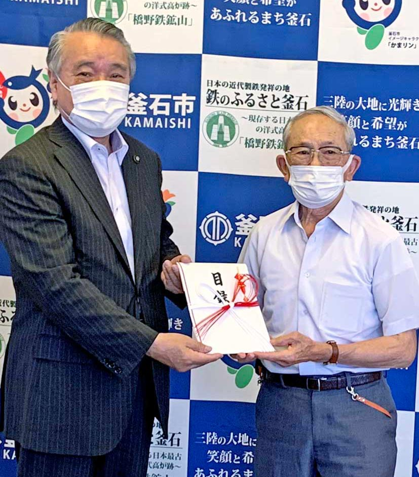 庁舎建設に役立ててもらおうと、野田市長に寄付金を託す佐々木さん(右)