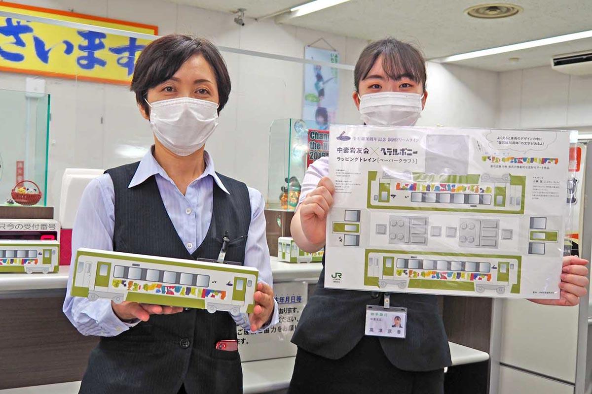 釜石線開業70周年記念ラッピング列車のペーパークラフトを手にする岩銀中妻支店の行員