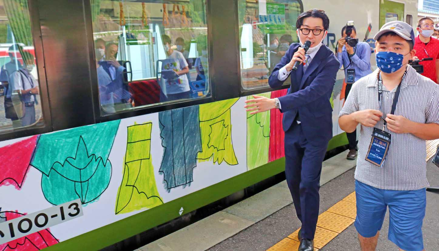 ヘラルボニーの松田文登副社長と車両を紹介する小林覚さん(右)
