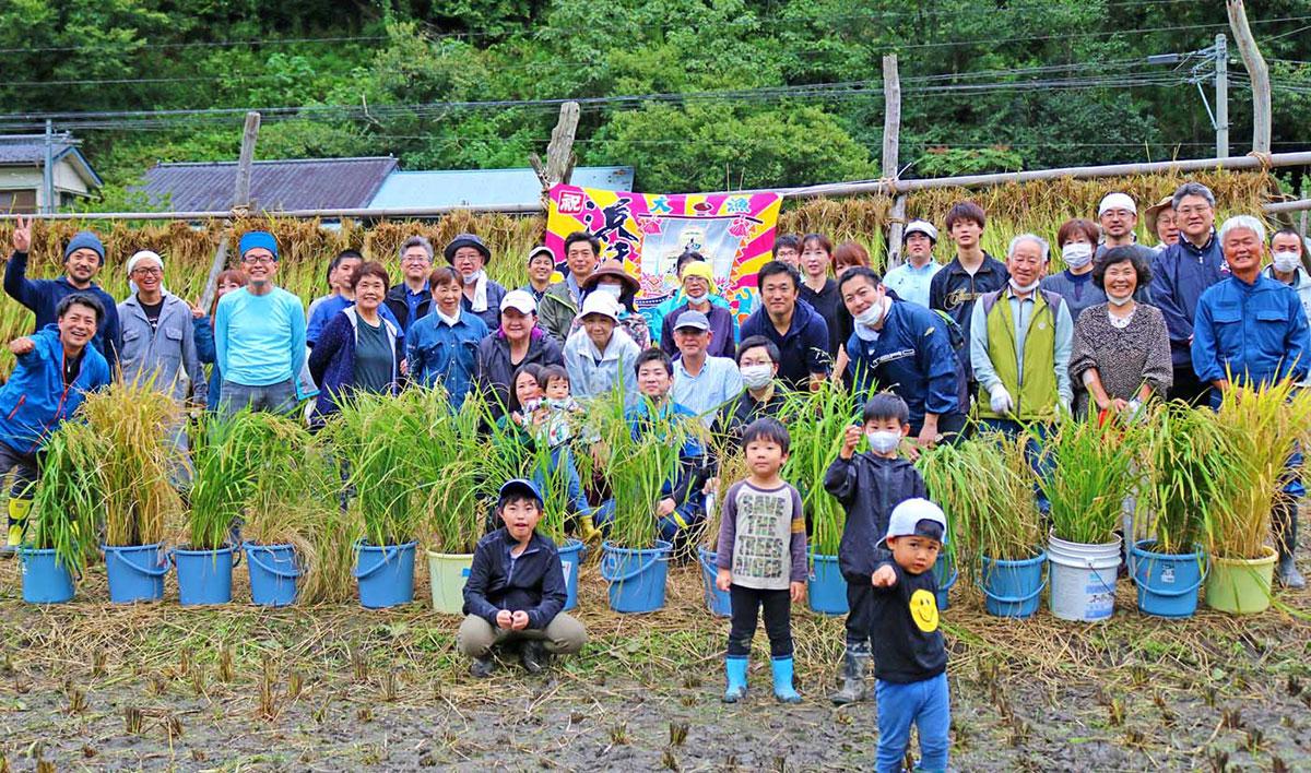 田んぼの稲刈りを終え、大きく成長したバケツ稲と記念撮影