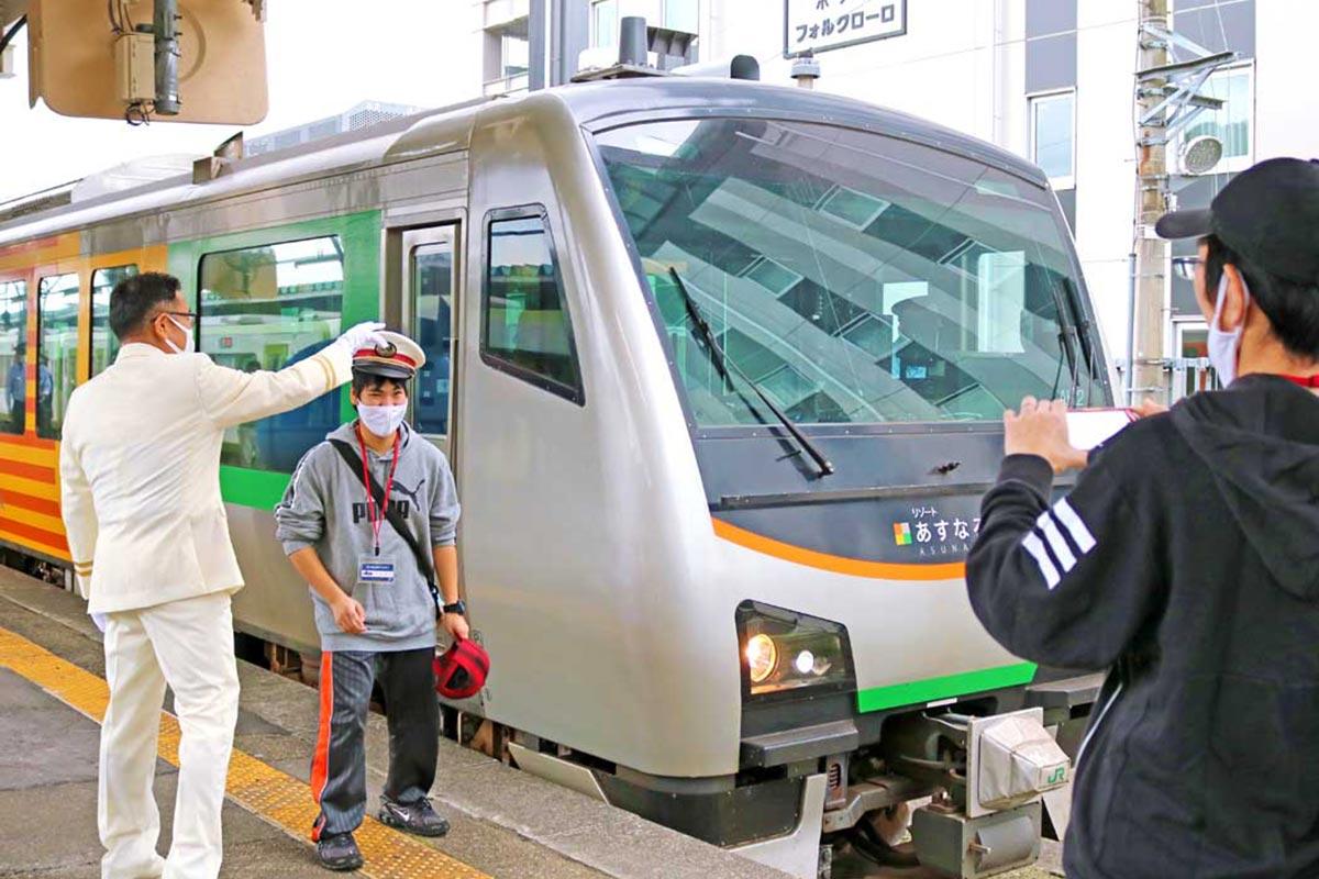 吉田駅長から制帽を借りて車両の前で記念撮影=釜石駅