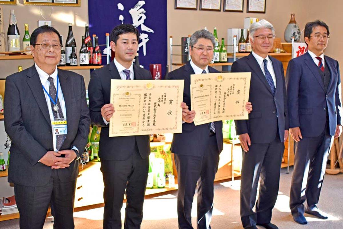 新里社長と奥村杜氏が賞状を受け、社員と共に栄誉を喜び合った