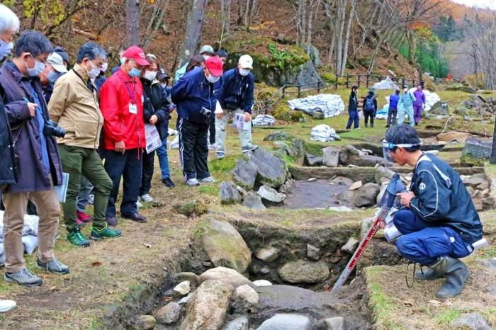 種砕水車場から続く排水路跡で説明を聞く見学者