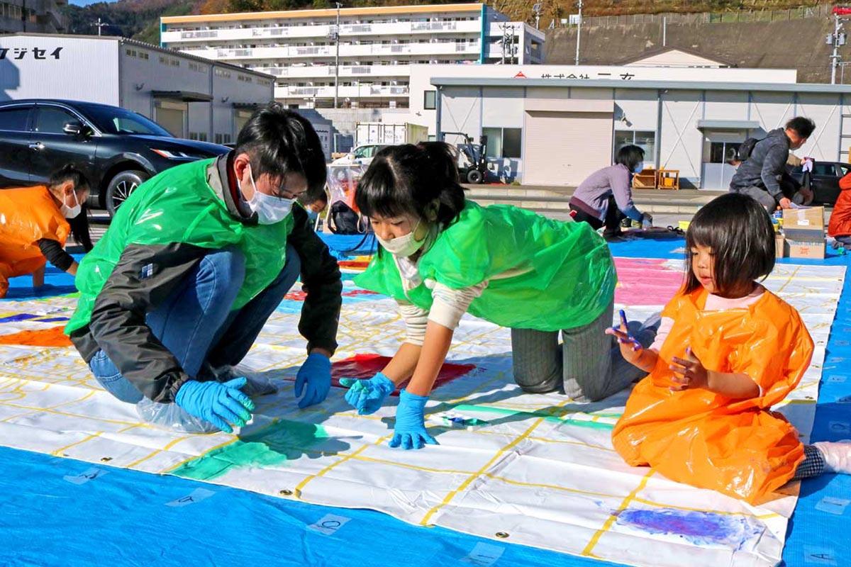 防水シートに描かれた絵に色を塗る参加者=22日