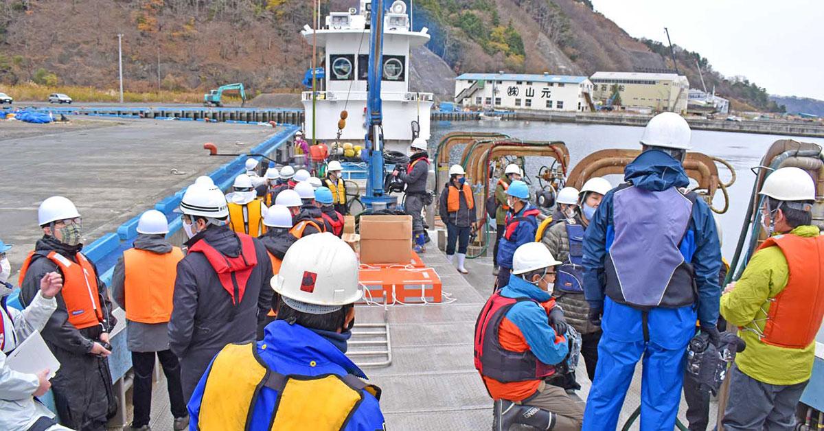 作業漁船に乗り込み、いけすに向かう関係者と報道陣