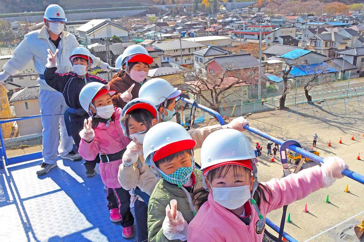 高所作業車に試乗し、「高いね」と笑顔を見せる児童