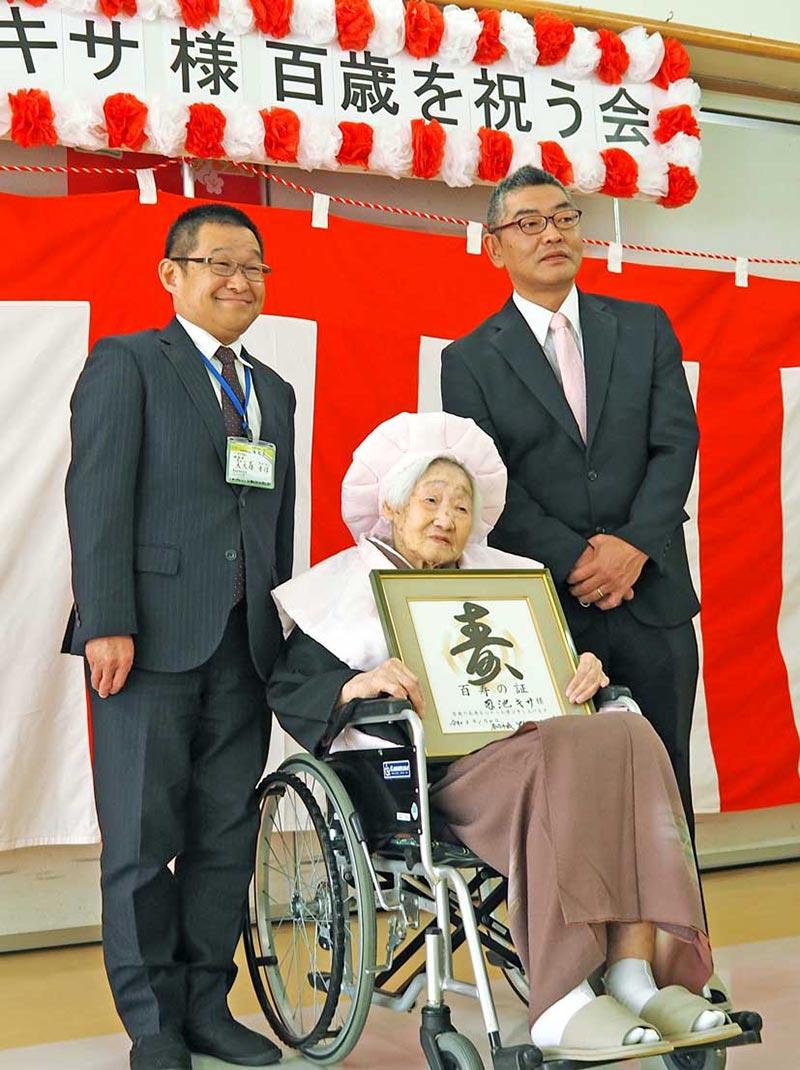 桃色のちゃんちゃんこと帽子を身に着けた100歳の菊池さん(中)、孫の荒田さん(右)