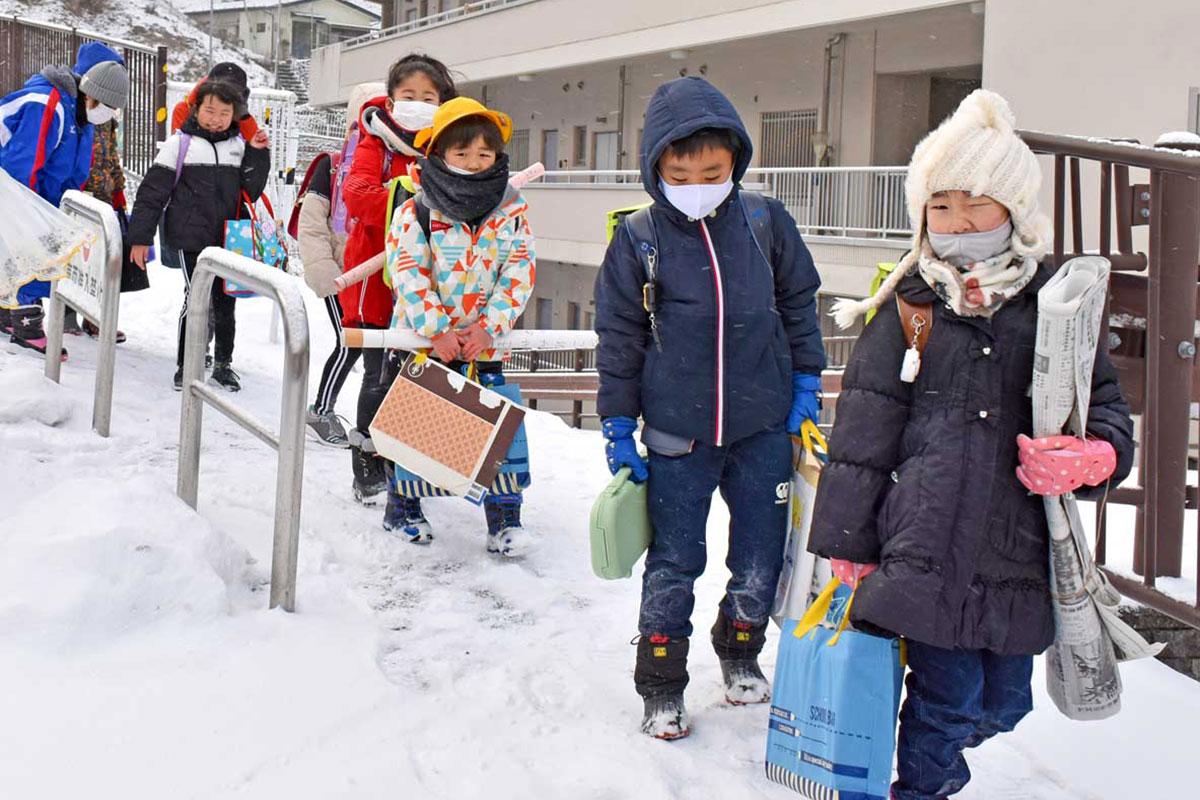 地吹雪模様の中、創作を両手に持って集団登校する白山小児童