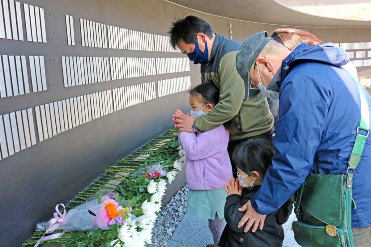 犠牲者の芳名板の前で祈りをささげる家族