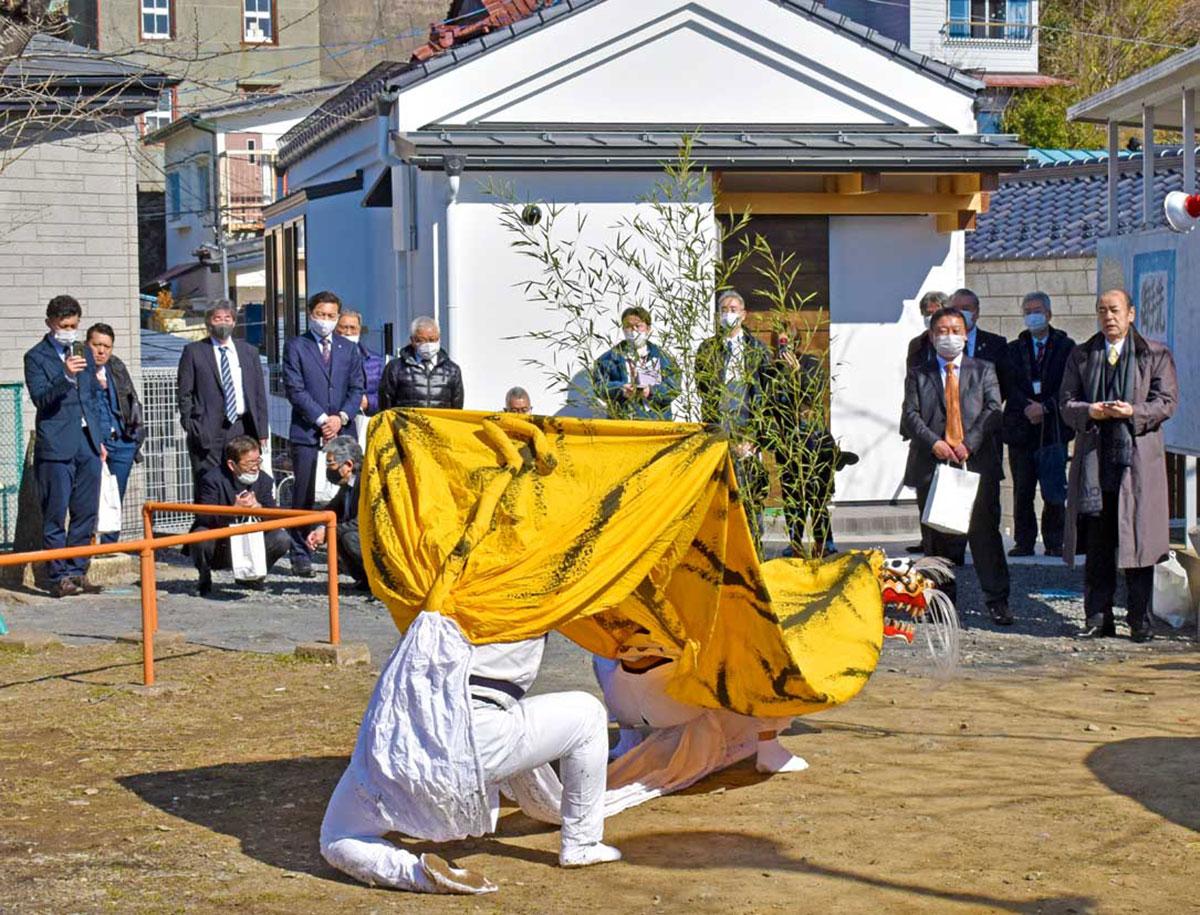 新たな練習拠点(正面)の完成を喜び、伝統の虎舞を威勢よく披露する尾崎青友会(台村公園)
