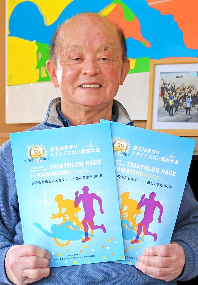 完成した記念誌を手に関係者に感謝の気持ちを表す小林会長