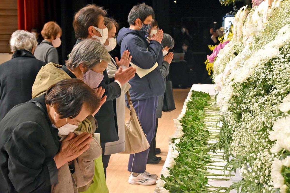 震災犠牲者に思いをはせ、追悼式で手を合わせる遺族ら