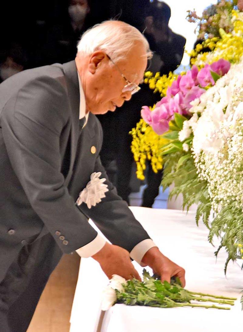 追悼の言葉を述べたあと花を手向ける鈴木堅一さん