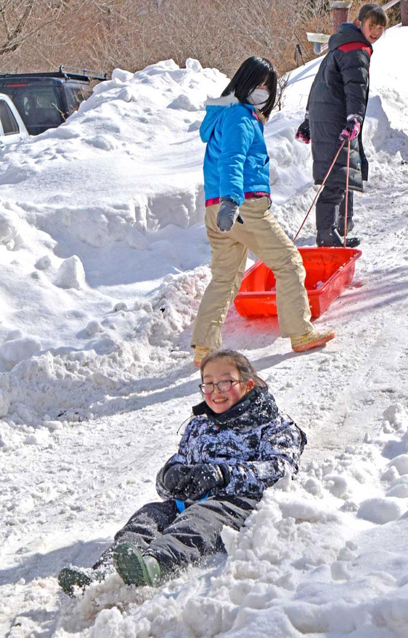雪まみれになって真冬のだいご味を楽しむこども