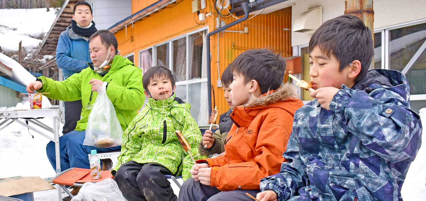 ストーブを囲み、小笠原さんの心尽くしで伝統の味を満喫する児童ら