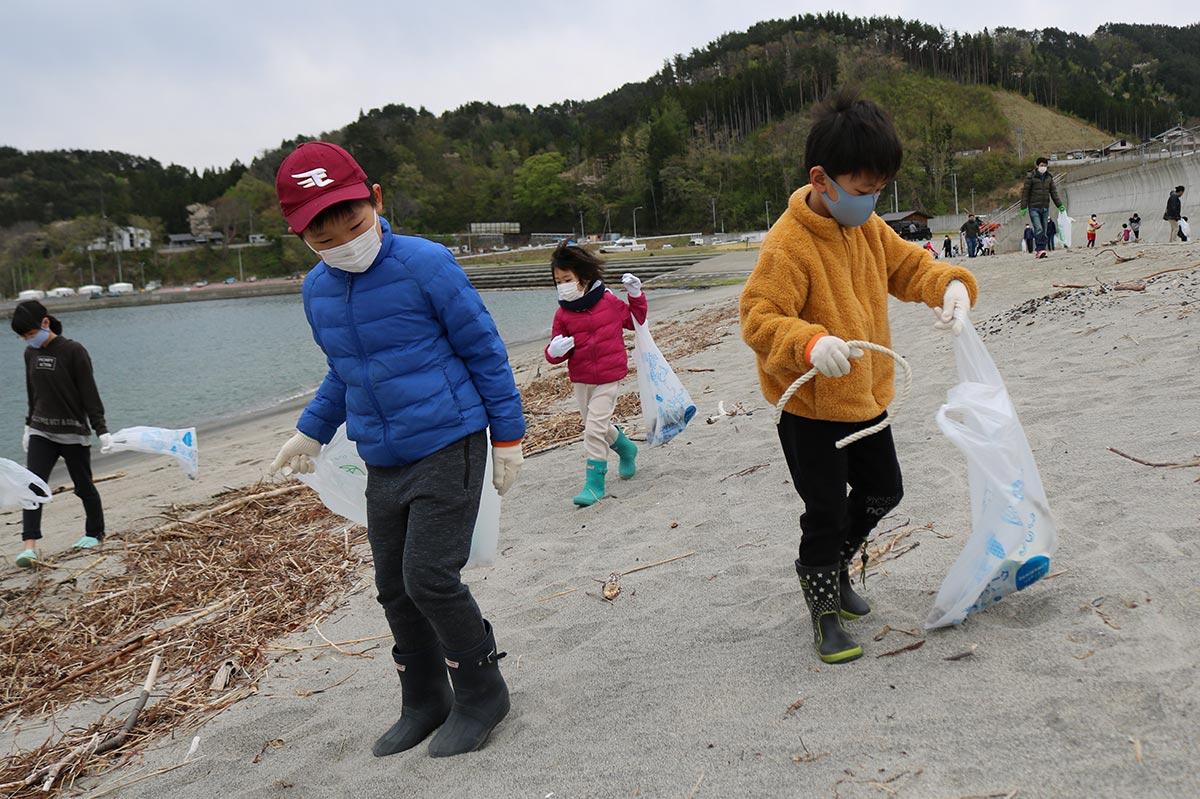 再生された根浜海岸の砂浜でごみを拾い集める子ども
