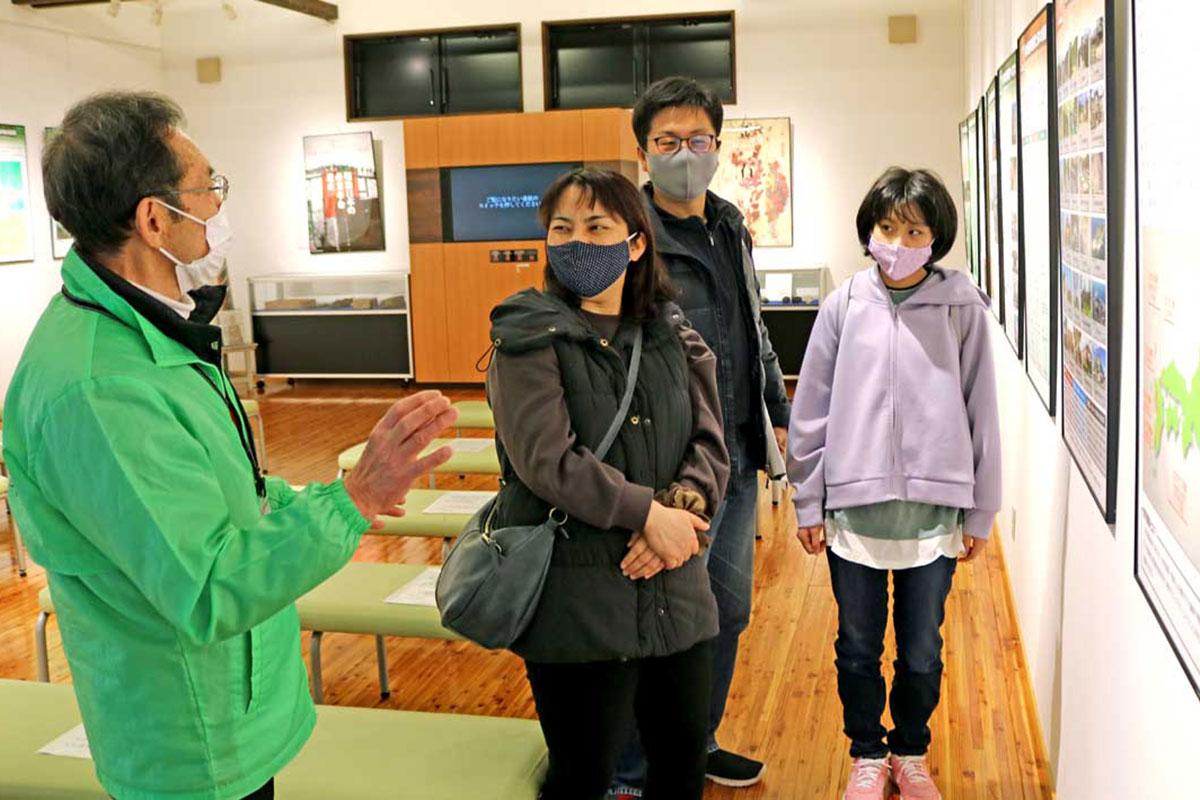 センターを訪れた見学者に説明する藤原信孝さん(左)