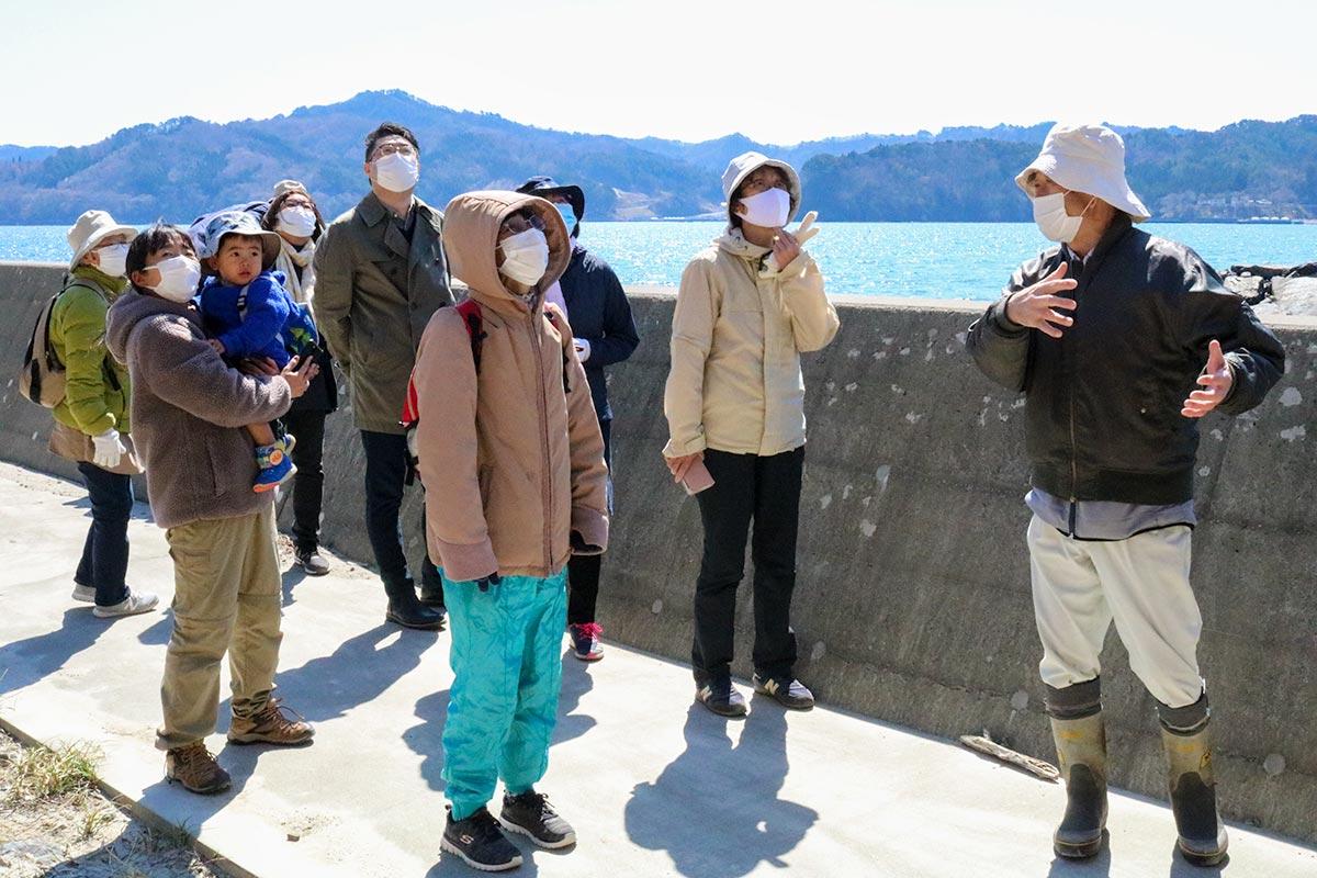 鈴木弘文会長(右)の解説に聞き入る参加者