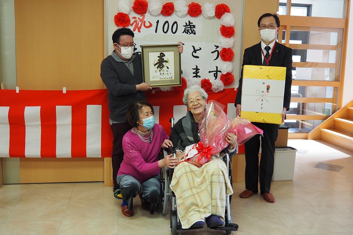 100歳の泉澤つねさん(前列右)、お祝いに訪れた親族や市関係者ら