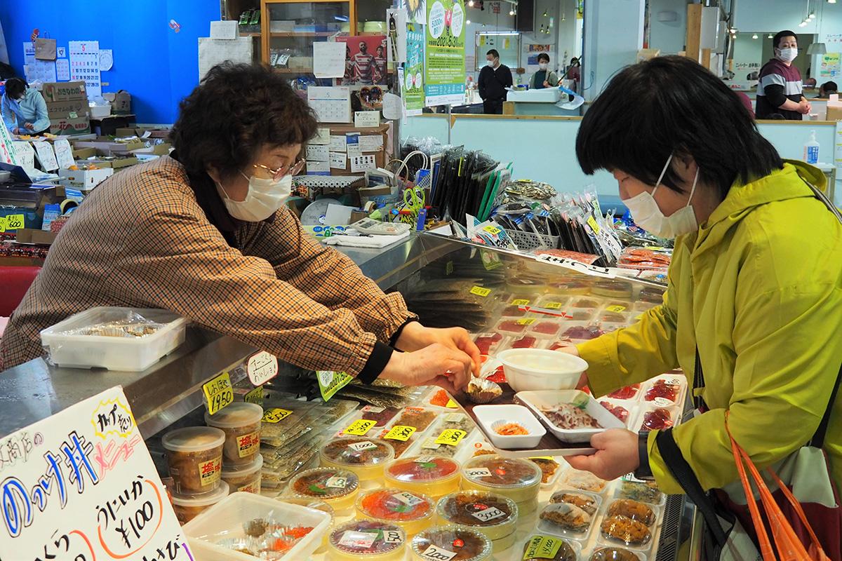 魚屋さんの助言を受けながら、丼にのせる具を求める女性(右)