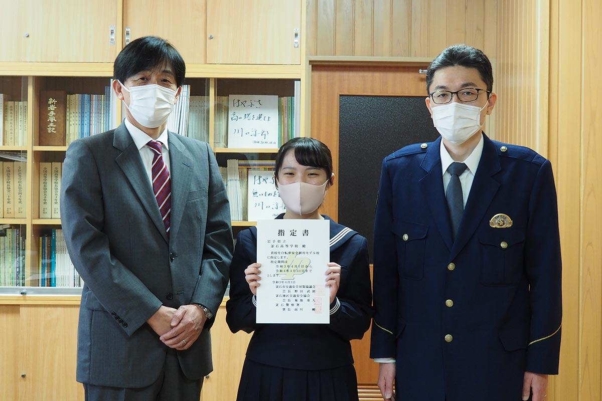 「自転車安全利用モデル校」の指定書を手にする釜石高の立花さん(中)、鈴木校長(左)