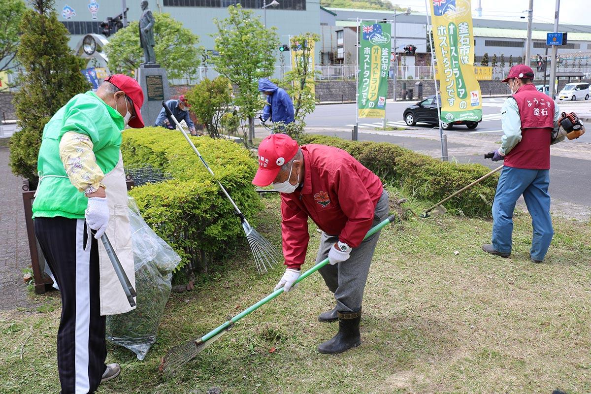釜石駅前広場で草刈り奉仕に励む観光ガイド会員ら