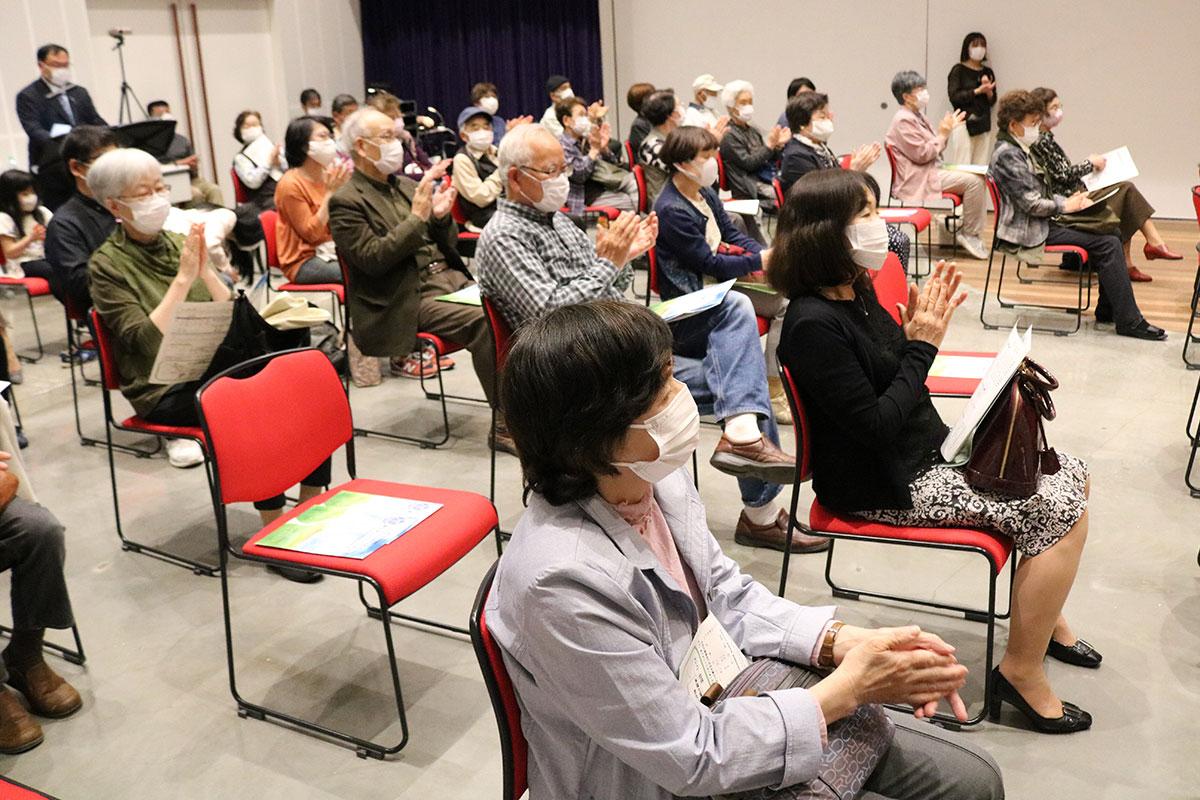 心温まるステージに感激し、団員に拍手を送る観客