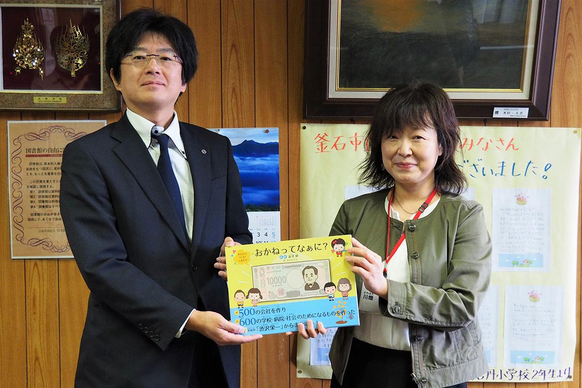 川畑館長に絵本を手渡した菊池会長(左)=釜石市立図書館