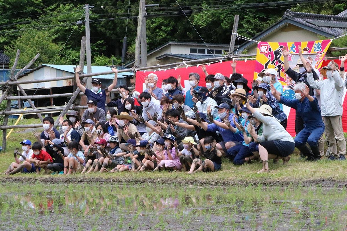 田植えを頑張った〝証し〟泥の付いた手を広げ、記念写真に収まる参加者