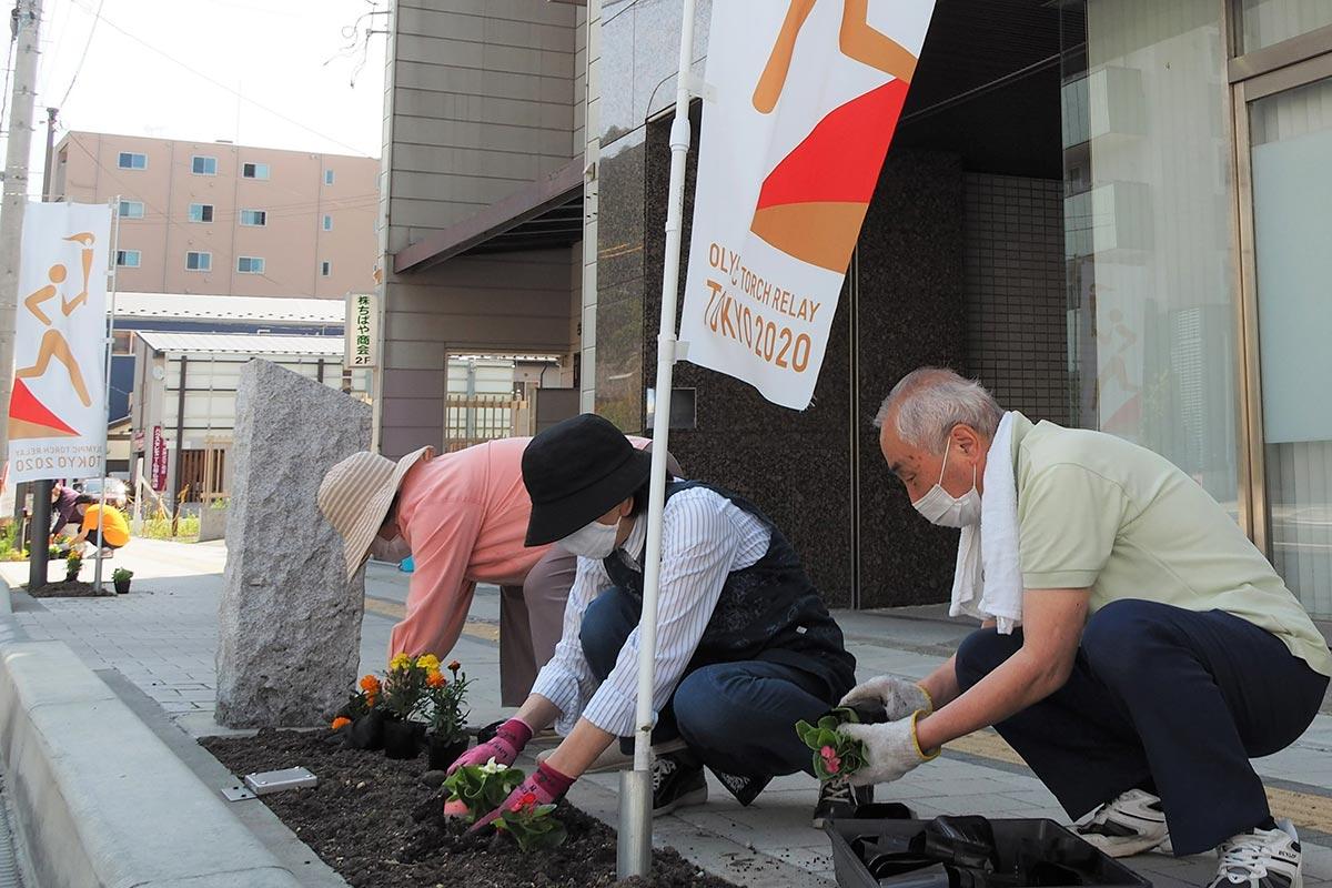 聖火リレーを盛り上げようと、市中心部の目抜き通りで植栽活動に取り組む大町町内会の会員ら=3日