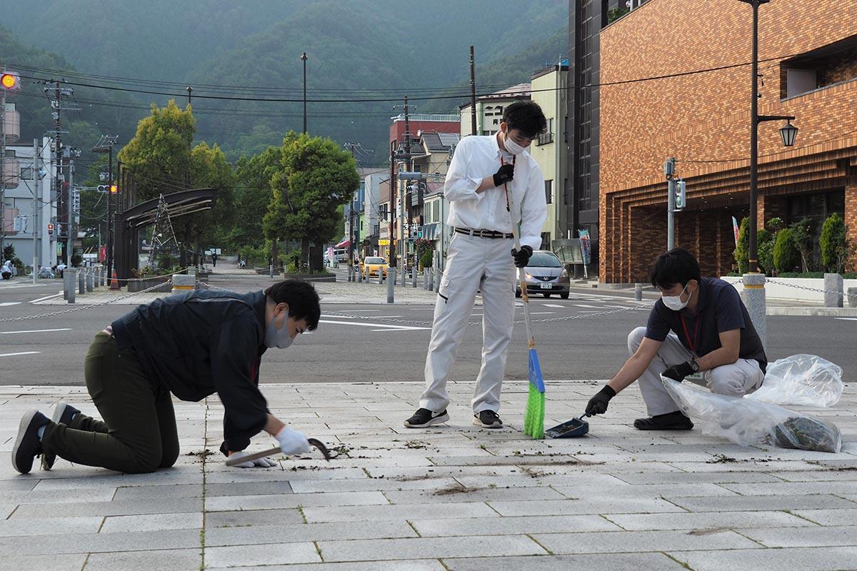 青葉通りの草取りに汗を流す市職員。気持ちよい環境で観覧してもらおうと取り組んだ=10日
