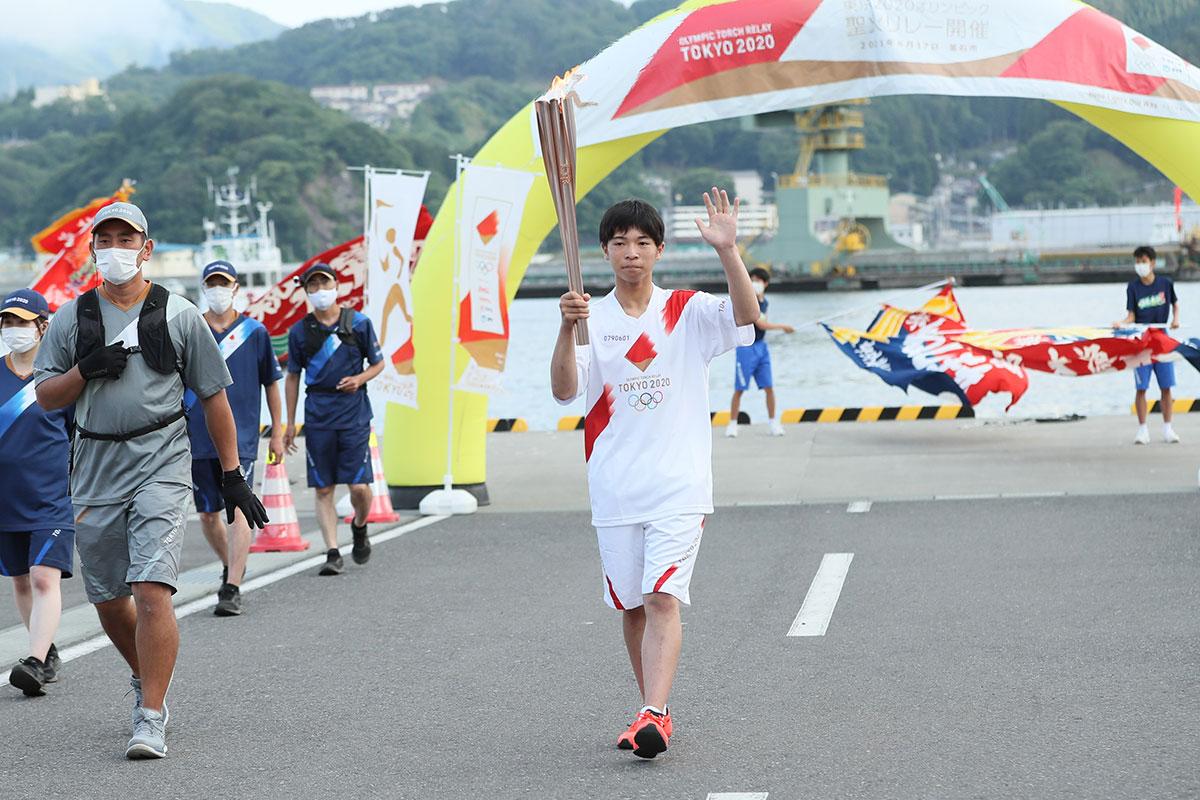 釜石市内第1走者を務めた奥村晄矢君。友達が大漁旗でエール(提供:東京2020組織委員会)