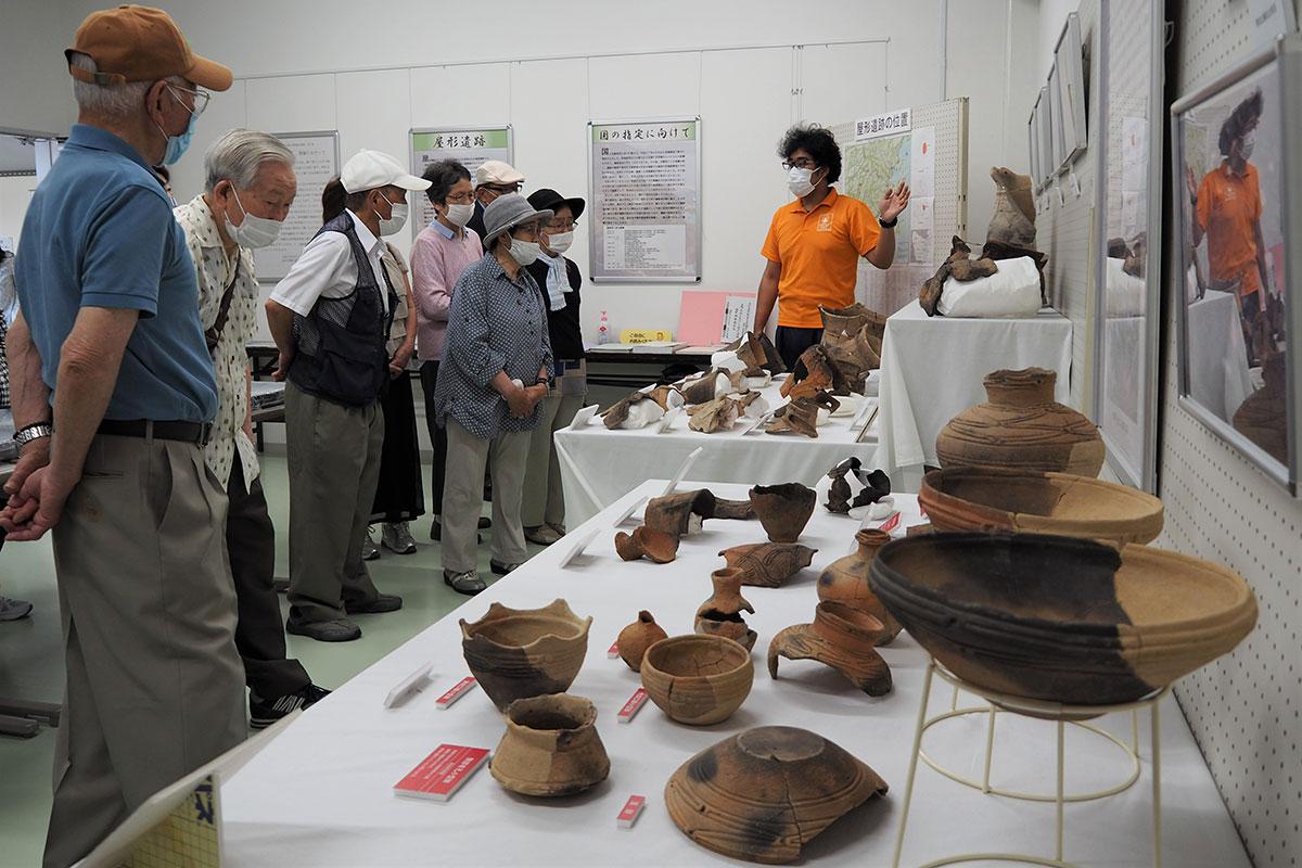 屋形遺跡から出土した土器や貝殻などが並ぶ市郷土資料館の企画展=14日