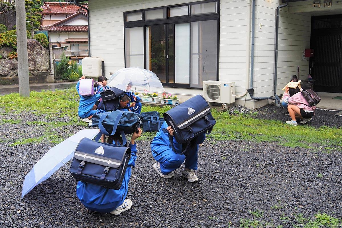 警報が流れると、児童生徒はその場でしゃがみ込んだり、カバンで頭を覆ったりして身を守った