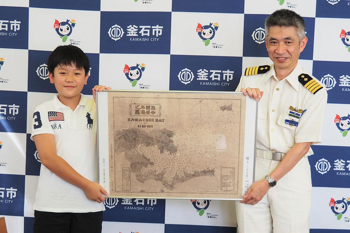 海図第1号の複製パネルを手にする松吉慎一郎部長(右)と山陰宗真君