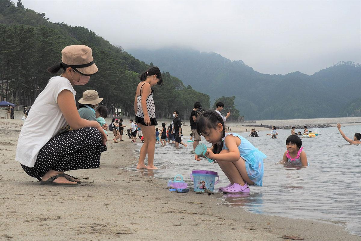 砂で遊んだり波と戯れたり、思い思いに海を満喫=22日