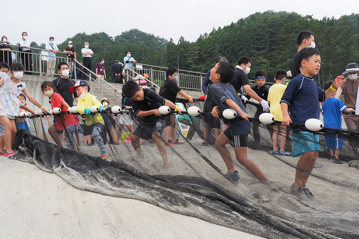 海開きに合わせて行われた関連イベントで、必死に網を引く子どもたち=22日