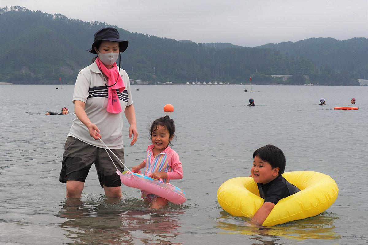 海開きした根浜海岸で水遊びを楽しむ親子連れ=22日