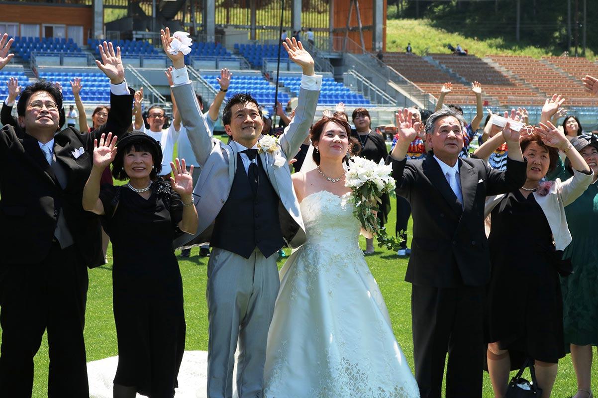 釜石鵜住居復興スタジアムで結婚式を挙げた本間和樹さん、えりさん夫妻(中央)