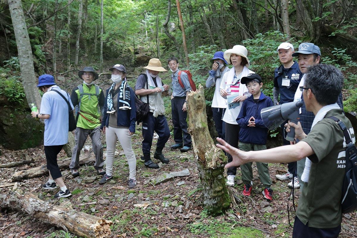 採掘場跡で説明を受ける参加者。写真奥のさらに登った場所には切り立った岩の下に半地下式の採掘場跡が残る