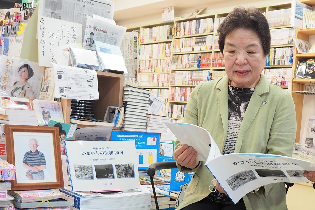 「潤さんも喜んでいると思う」。店頭に並んだ戦災記録誌を見つめる岩切久仁さん=釜石市大町・桑畑書店