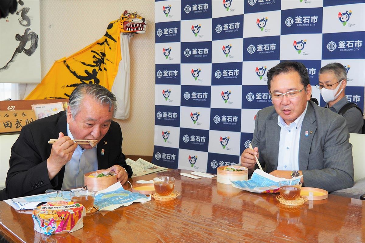 一つ一つの料理に関する説明を確認しながらジオ弁を味わう野田市長(左)ら=8月5日、釜石市役所