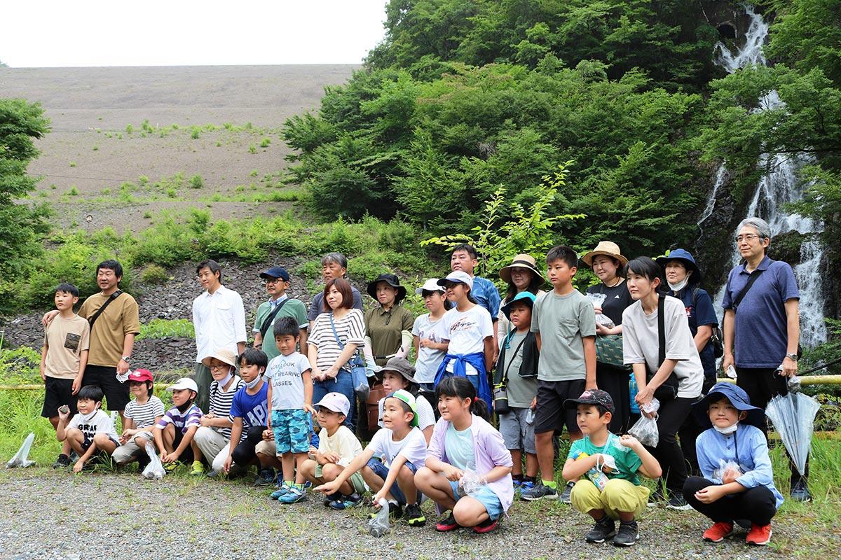 選鉱で出た廃石が積み上げられた堆積場(高さ120メートル)と人工の滝に囲まれ記念撮影