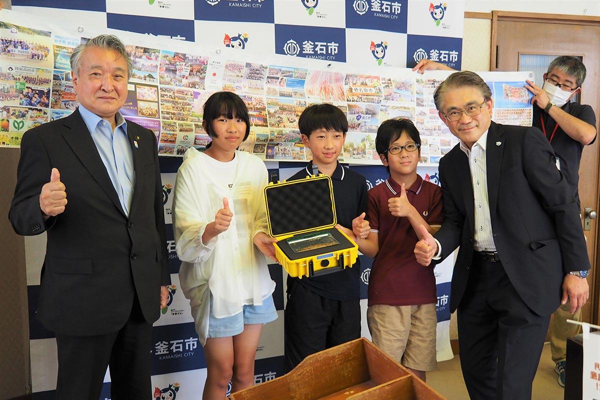 ハマユリの種を手に笑顔でポーズを決める釜石小児童、長谷川代表理事(右)、野田市長(左)